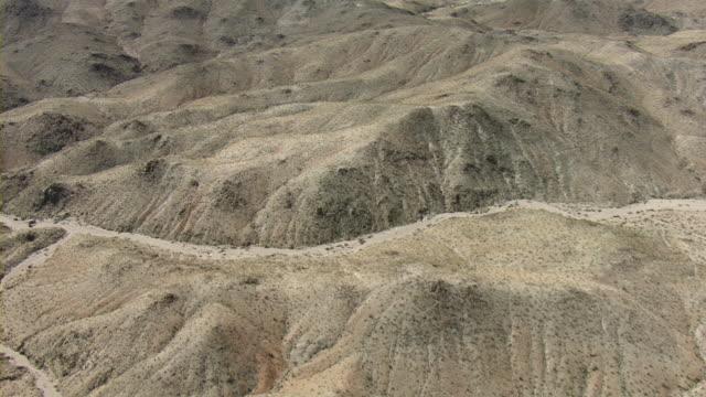 A dirt trail runs between tall, crusted sand dunes in the vast, arid Nevada desert.