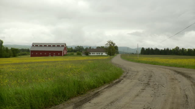 stockvideo's en b-roll-footage met ws dirt winding road crossing green fields with barn / morristown, vermont, usa - boerderijschuur