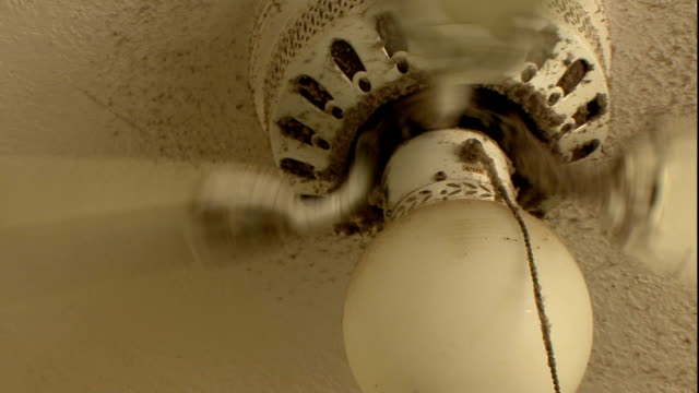 a dirty ceiling fan spins counter-clockwise. - ceiling fan stock videos & royalty-free footage