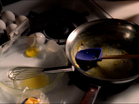 Dirty dishes sit on a stove top next to a plate of eggs and toast.