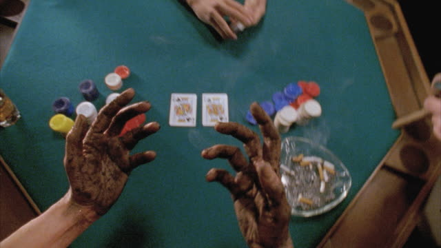 CU POV Dirty hands of man holding cigar and alcoholic drink by gambling table / New York City, New York, USA