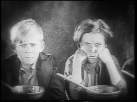 b/w 1922 2 dirty orphan boys pouting by bowls of gruel / feature - orphan stock videos & royalty-free footage