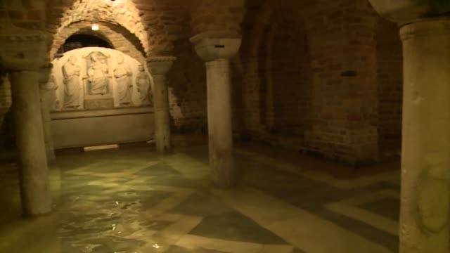 dirty water swirls around marble tombs inside the 12th century crypt of st mark's basilica in venice which suffered untold damage when an... - crypt stock videos & royalty-free footage