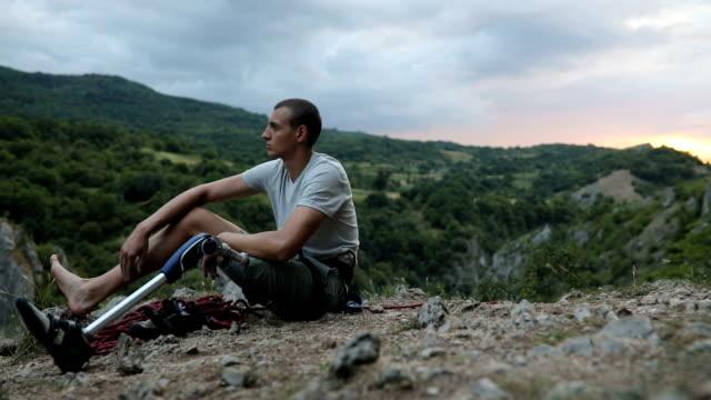 stockvideo's en b-roll-footage met handicap kerel klimmer rusten - prothesen