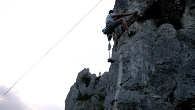 stockvideo's en b-roll-footage met arbeidsongeschiktheid man houdt van klimmen - prothesen