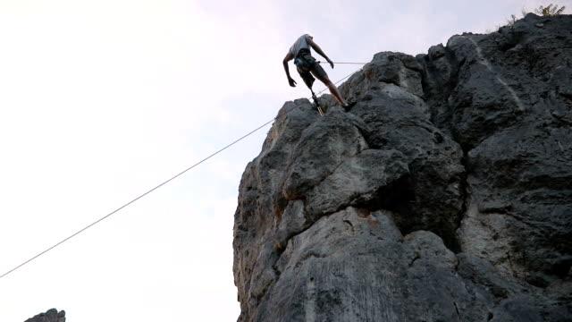 stockvideo's en b-roll-footage met arbeidsongeschiktheid man klimmen op de rotsen - prothesen