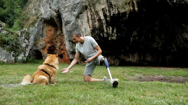 stockvideo's en b-roll-footage met arbeidsongeschiktheid man met hond - prothesen