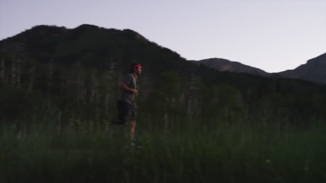 WS PAN Disabled athlete with artificial limb jogging in mountains at sunset / American Fork Canyon, Utah, USA