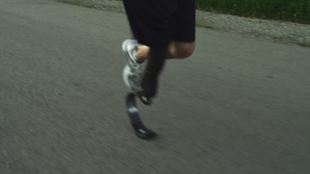 ms slo mo ts tu disabled athlete with artificial limb jogging on rural road / american fork canyon, utah, usa - artificial limb stock videos & royalty-free footage