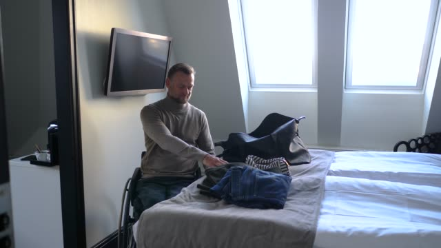 disabled businessman looking at digital camera by bed in hotel room - digital camera stock videos & royalty-free footage
