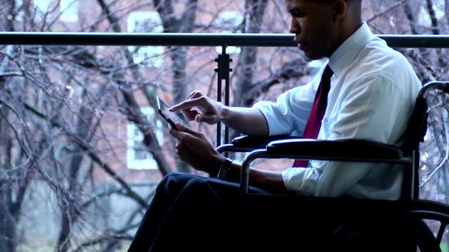 disabili uomo d'affari con computer tablet-mcu - sedia a rotelle video stock e b–roll