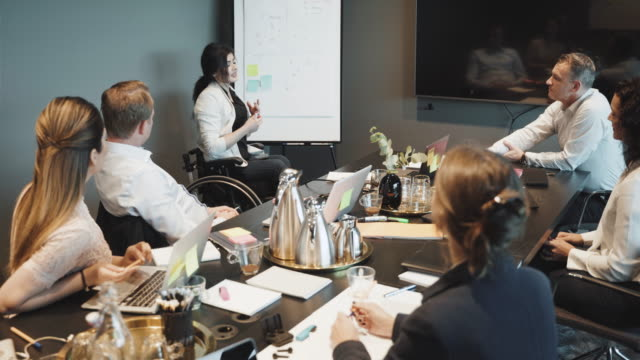 disabled businesswoman gesturing while explaining during meeting in board room - employee engagement stock videos & royalty-free footage