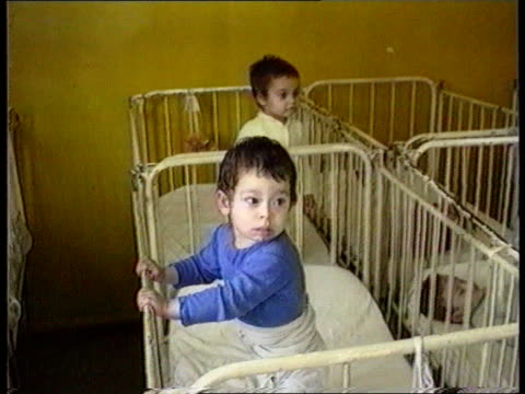 disabled children; itn lib romania tms baby tied in cot crying babies standing in cots as rocking child looking out from cot tcms child in bed - romania点の映像素材/bロール
