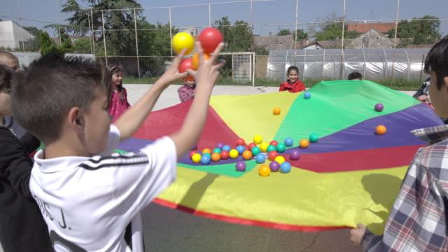 vídeos de stock e filmes b-roll de disabled children throwing balls in the air from parachute - estilo de vida alternativo