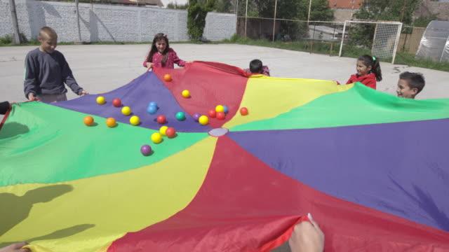 vídeos de stock, filmes e b-roll de crianças deficientes jogando bolas no ar com paraquedas - sacudindo