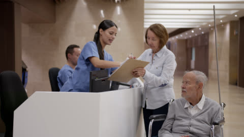 disabled elderly man being registered at the hospital by his companion at the nurses station - medical clinic stock videos & royalty-free footage