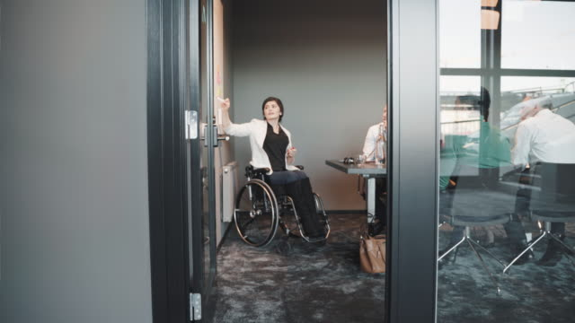 disabled female executive explaining over whiteboard to multi-ethnic colleagues in board room of creative office - employee engagement stock videos & royalty-free footage