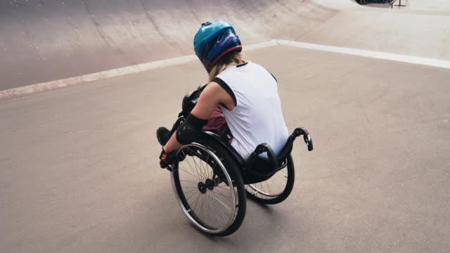 behinderte generation-z frau im rollstuhl macht stunts im skatepark - stunt stock-videos und b-roll-filmmaterial