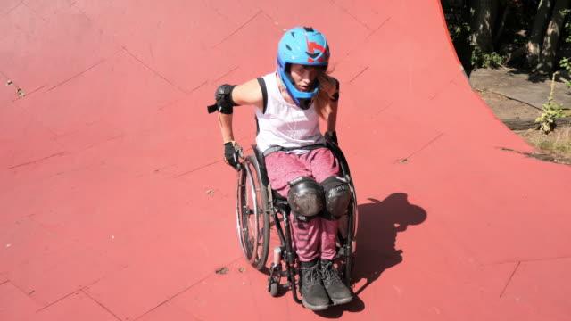 behinderte generation-z frau im rollstuhl macht stunts im skatepark - aktivitäten und sport stock-videos und b-roll-filmmaterial