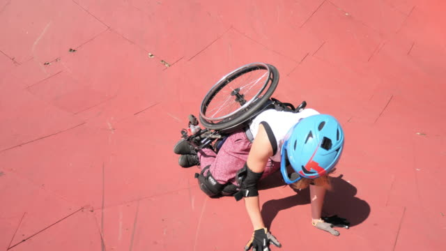 stockvideo's en b-roll-footage met gehandicapte generatie-z vrouw in rolstoel stunts doen in skatepark en vallen - skateboardpark