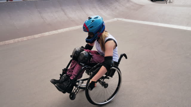disabled generation-z woman in wheelchair doing stunts in skate park - helmet stock videos & royalty-free footage