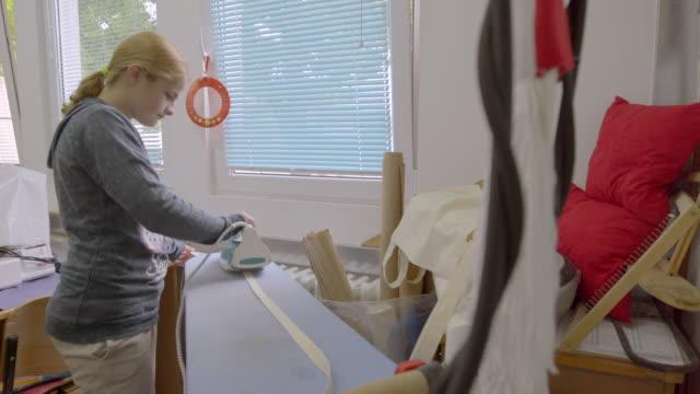 学校で縫製のクラスで障害のある女の子アイロンストラップ - 依存点の映像素材/bロール