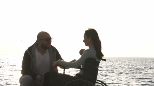 vidéos et rushes de fille handicapée sur le fauteuil roulant avec son petit ami au bord de la mer - chaise roulante