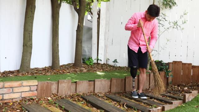 vídeos y material grabado en eventos de stock de hombre discapacitado con una pierna protésica barriendo su patio trasero - barrer