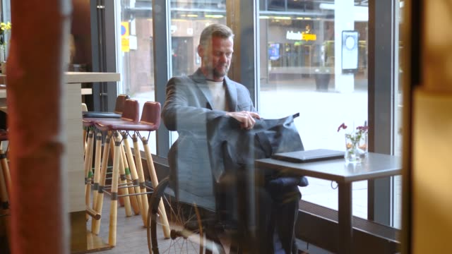 disabled mature businessman removing laptop from bag in restaurant at hotel - laptop bag stock videos and b-roll footage