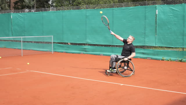 vídeos de stock e filmes b-roll de disabled men playing wheelchair tennis outdoors - cadeira de rodas