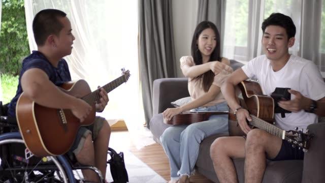 vidéos et rushes de musicien handicapé joue de la guitare avec un ami. - équipement médical