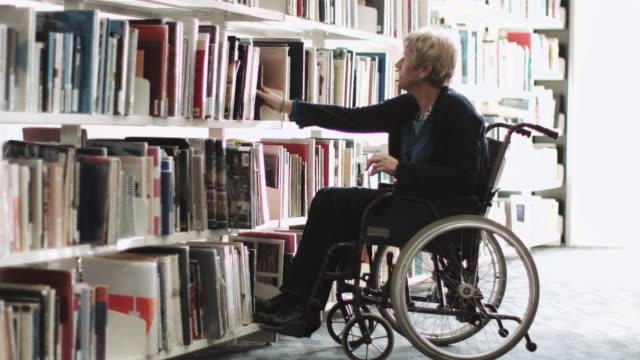 vídeos y material grabado en eventos de stock de disabled senior adult female in wheelchair in library - biblioteca