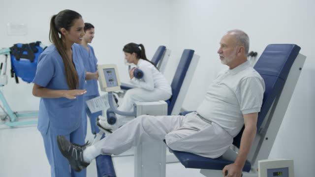 behinderter senior-mann stärkt sein bein während der physiotherapie mit anderen fachleuten und patienten - amputiert stock-videos und b-roll-filmmaterial