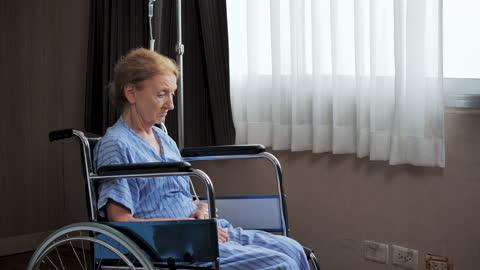 vídeos y material grabado en eventos de stock de mujer mayor discapacitada sentada sola en silla de ruedas en el hospital. - demencia