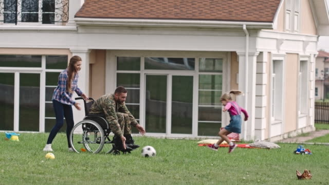 Disabled soldier in wheelchair playing ball with daughter