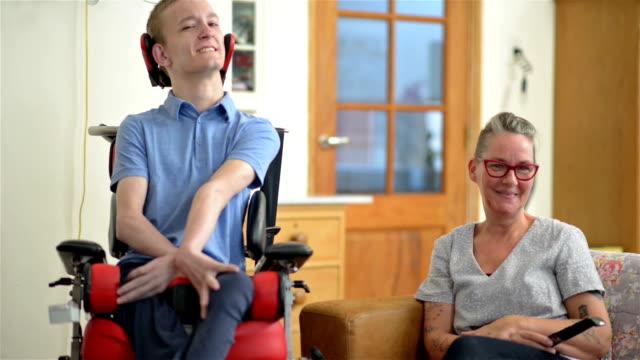 vídeos y material grabado en eventos de stock de hijo discapacitado con su madre - asistente sanitario
