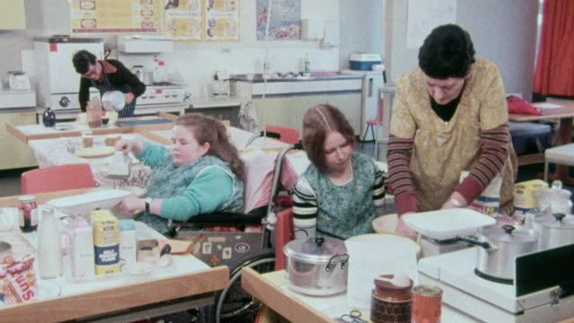 stockvideo's en b-roll-footage met montage disabled students cooking in a kitchen and checking a braille watch for the time / united kingdom - home economics