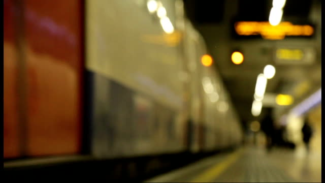 disabled travel around london; lib int soft focus shot of underground train along into station ext people to and fro in street - soft focus stock videos & royalty-free footage