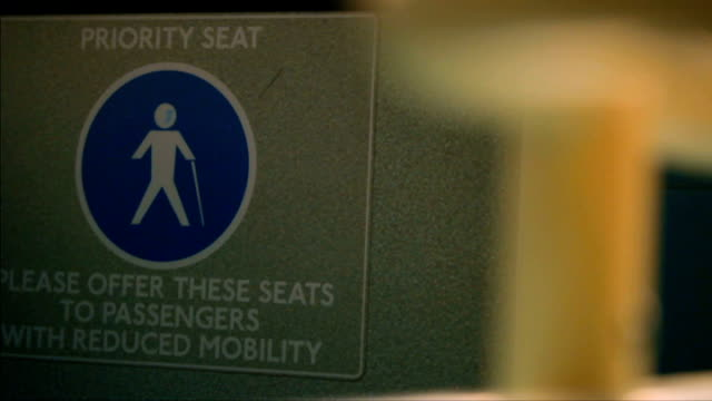 Disabled travel around London LIB INT PAN to 'Priority Seat' sign FOCUS sign 'Buggy users please make space for wheelchair users' Passenger in...
