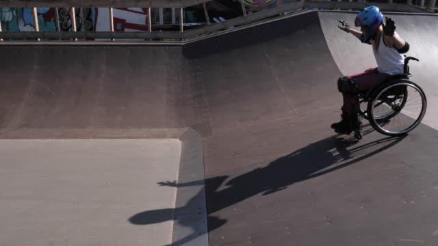 vídeos y material grabado en eventos de stock de mujer discapacitada en silla de ruedas haciendo acrobacias en el parque de patinaje - generation z