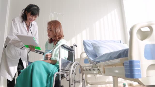 障害のある女性は、車椅子に座って働き、病院でデジタルタブレットを使用しています - 骨折点の映像素材/bロール