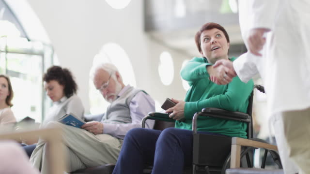 Disabled woman talking with Doctor in waiting room