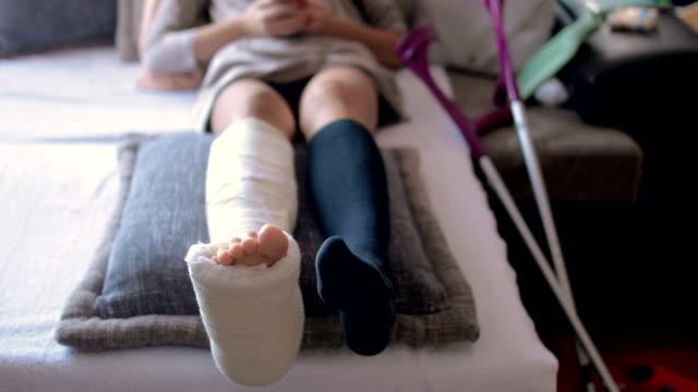 スマートフォンを使用して自宅で足と石膏の足を骨折した障害のある女性 - 骨折点の映像素材/bロール
