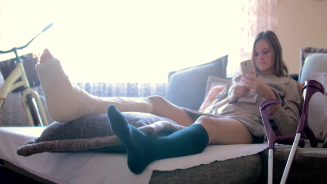 disabled woman with broken leg and plaster foot at home using smart phone - misfortune stock videos & royalty-free footage