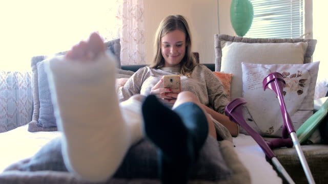 disabled woman with broken leg and plaster foot at home using smart phone - bandage stock videos & royalty-free footage
