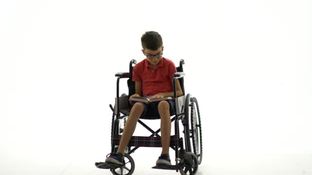 disabled young boy reading book - plain background stock videos & royalty-free footage