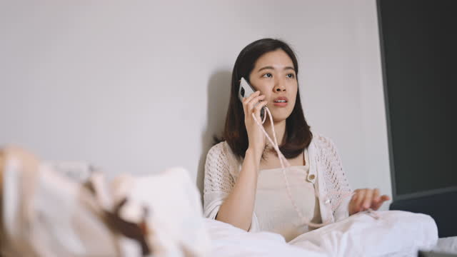 disappointed and stress young asian woman having unpleasant phone talk to her friend in her domestic room - worried stock videos & royalty-free footage