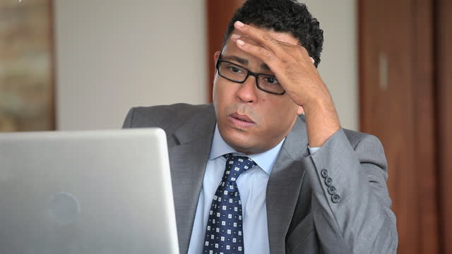 disappointed businessman using laptop in office - disappointment stock videos & royalty-free footage