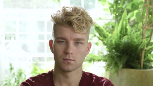 Disappointed young man with blonde hair looking at camera.