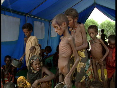 Relief problem SOMALIA Bardera R flooded river LS People on river bank INT/TENT TMS Thin children sitting on ground as food ladled out EXT TCMS Thin...